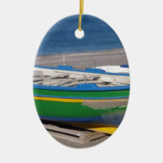 Old green fishing boat on beach. ceramic oval decoration