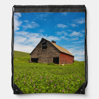 Old, red barn in field of chickpeas drawstring bag