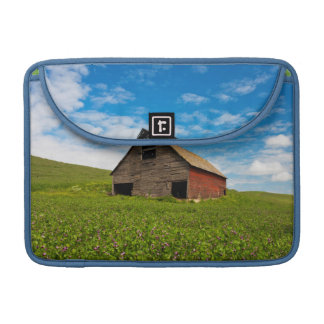 Old, red barn in field of chickpeas sleeve for MacBooks