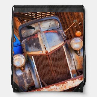 Old rusty truck on a farm drawstring bag