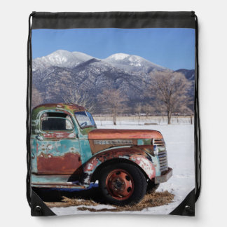 Old truck sitting in the field drawstring bag