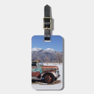 Old truck sitting in the field luggage tag