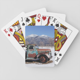 Old truck sitting in the field playing cards
