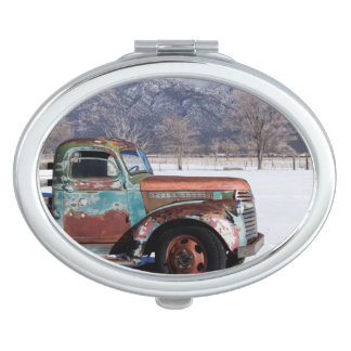 Old truck sitting in the field vanity mirrors