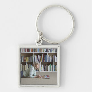 Older woman reading by bookshelves key ring