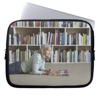 Older woman reading by bookshelves laptop sleeve
