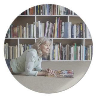 Older woman reading by bookshelves plate