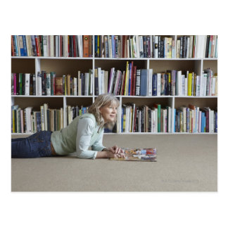 Older woman reading by bookshelves postcard