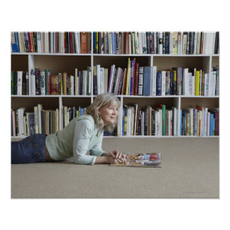 Older woman reading by bookshelves print