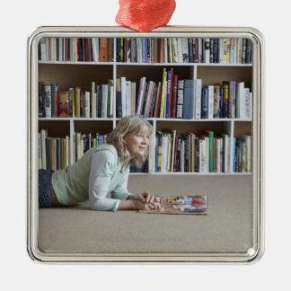 Older woman reading by bookshelves Silver-Colored square decoration
