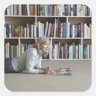 Older woman reading by bookshelves square sticker