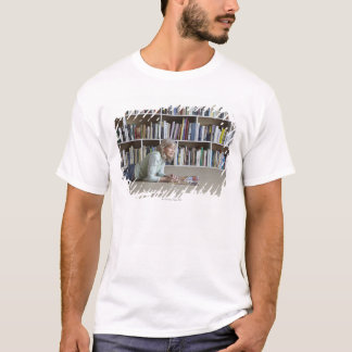 Older woman reading by bookshelves T-Shirt