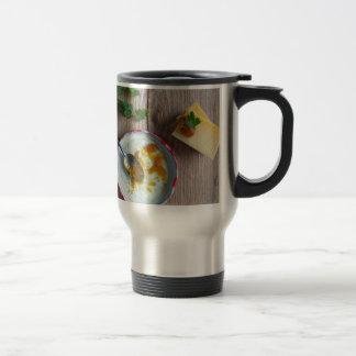 Onion pineapple chutney on rustic wood stainless steel travel mug