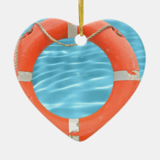 Orange lifebuoy over swimming pool water backgroun ceramic heart decoration