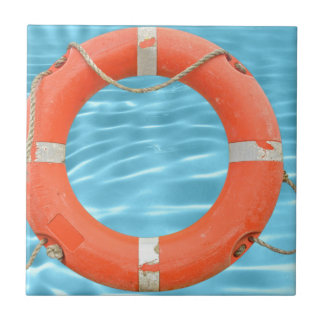 Orange lifebuoy over swimming pool water backgroun small square tile