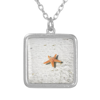Orange starfish on a white sandy beach silver plated necklace