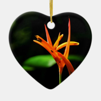 Orange tropical flowers isolated against black bac ceramic heart decoration