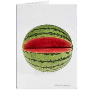 Organic watermelon with a slice cut into it, on card