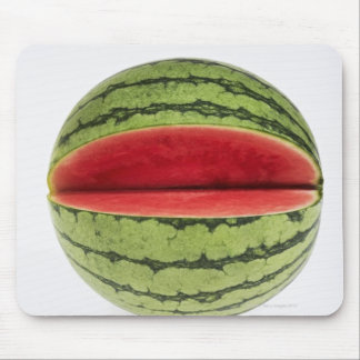 Organic watermelon with a slice cut into it, on mouse mat