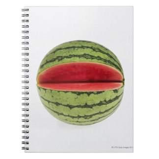 Organic watermelon with a slice cut into it, on spiral notebook