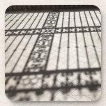 ornate iron fencing shadow on tile floor beverage coaster
