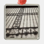 ornate iron fencing shadow on tile floor christmas ornament