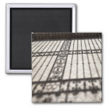 ornate iron fencing shadow on tile floor square magnet