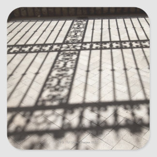 ornate iron fencing shadow on tile floor square sticker