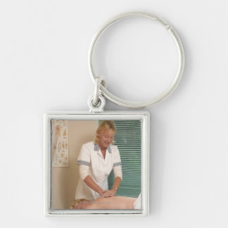 Osteopath/chiropractor manipulating back Silver-Colored square key ring