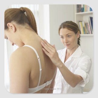Osteopath treating patient. square sticker