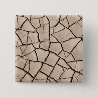 overhead view of cracked earth on a desert 15 cm square badge