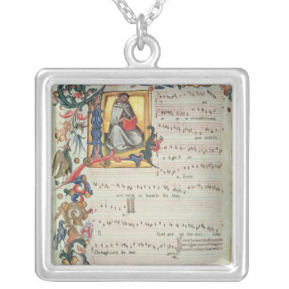 Page of musical notation with a historiated silver plated necklace