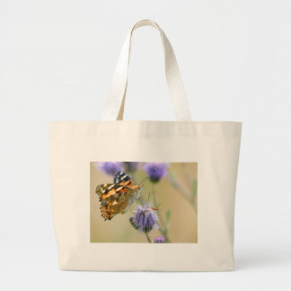 Painted lady butterfly feeding on blue flower canvas bag