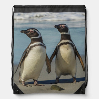Pair of penguins on the beach drawstring bag