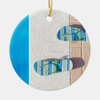 Pair of slippers at edge of swimming pool christmas ornament
