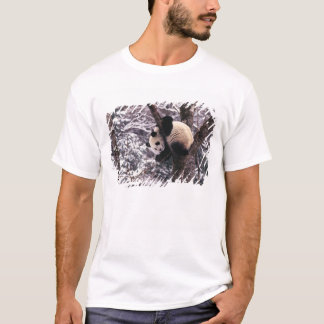 Panda cub playing on tree covered with snow, T-Shirt
