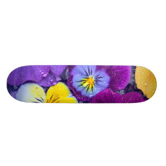 Pansy flowers floating in bird bath with dew 2 skate deck