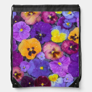 Pansy flowers floating in bird bath with dew drawstring backpacks
