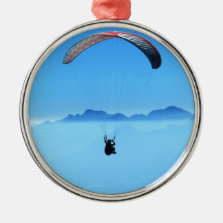 Paraglider on blue background with mountains Silver-Colored round decoration