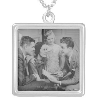Parents and daughter (6-7) talking with male silver plated necklace