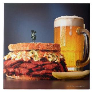 Pastrami sandwich with mug of beer tile