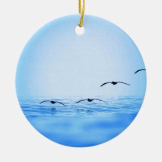 Pelicans flying over ocean christmas ornament