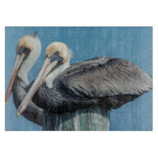 Pelicans roosting on pylon cutting board