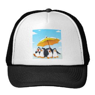 Penguins standing under umbrella cap