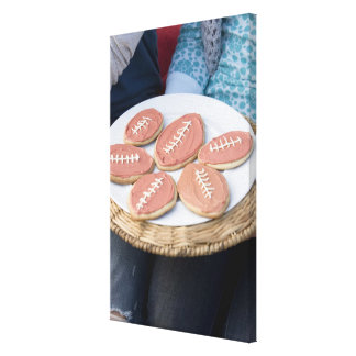 People holding plate of football cookies canvas print