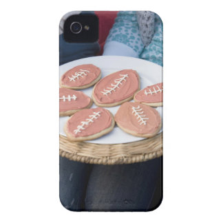 People holding plate of football cookies iPhone 4 covers