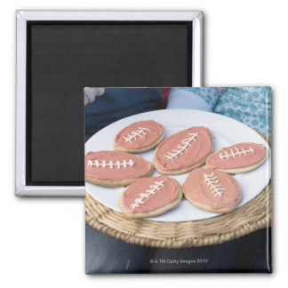 People holding plate of football cookies magnet