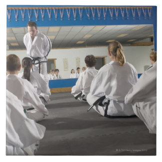 People in a tae kwon do class large square tile