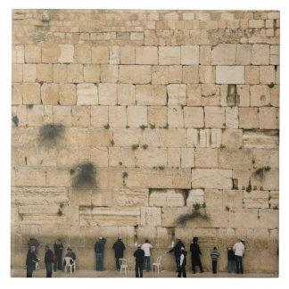 People praying at the wailing wall large square tile