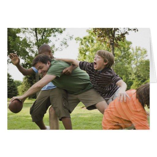 People tackling while playing football greeting card